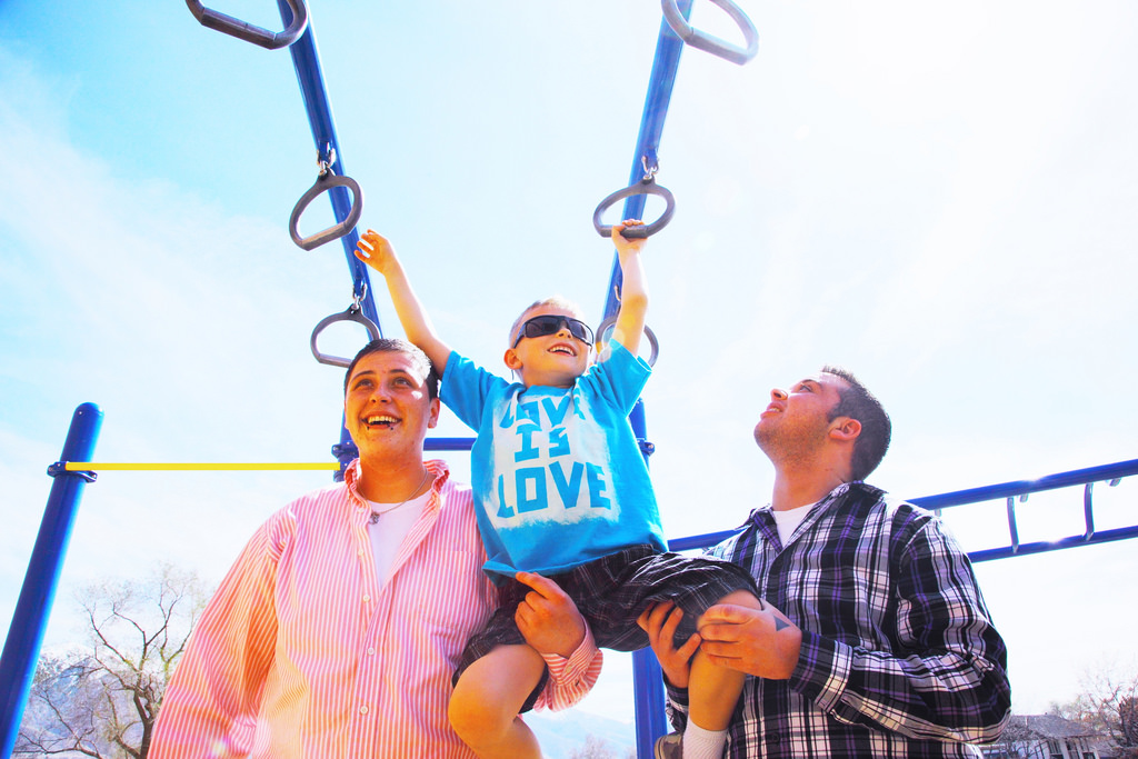 Gay dads playing with son on playpark