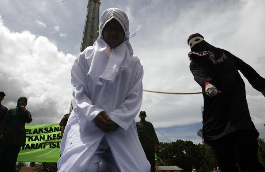 camera is angled up to see a women wearing a white hijab who is kneeling and is being caned by a person whose face and body is covered behind her. She is grimacing in pain