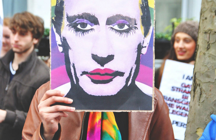 Protestor holds poster over their face of Putin wearing makeup on top of a rainbow background