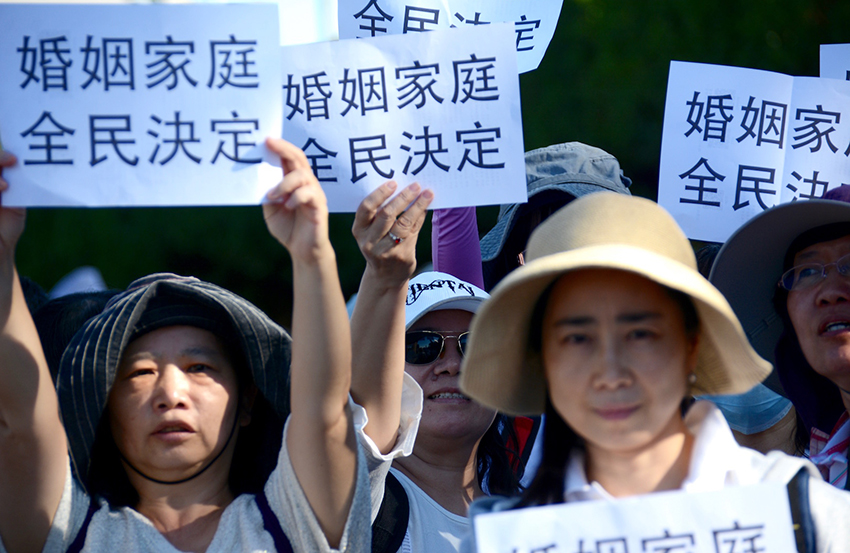 Women hold banners against same-sex marriage in Taiwan.