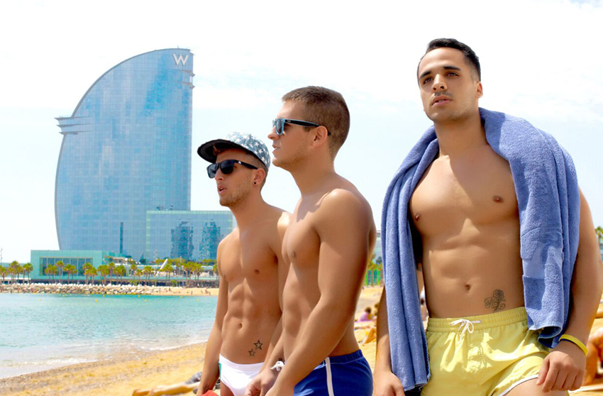Guys soak up the sun along the Barceloneta boardwalk, with the W Barcelona standing tall behind them