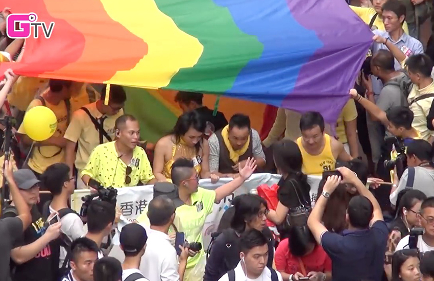 a large crowd of people standing under a pride flag in hong kong