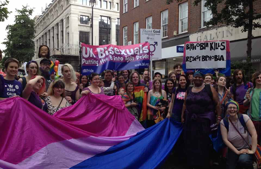Bisexuals at Pride in London holding a bit bisexual flag