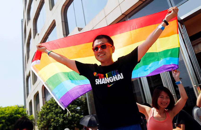 A celebrator at Shanghai Pride waves a rainbow flag