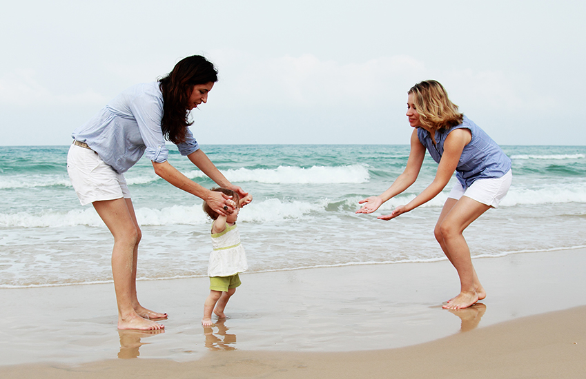 Female couple and child on a beach.