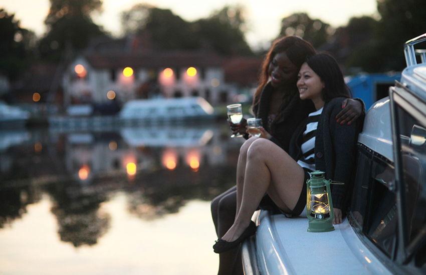 A female couple relax on a Hoseasons boat at sunset.