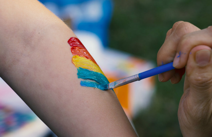 A rainbow being painted on someone's arm.