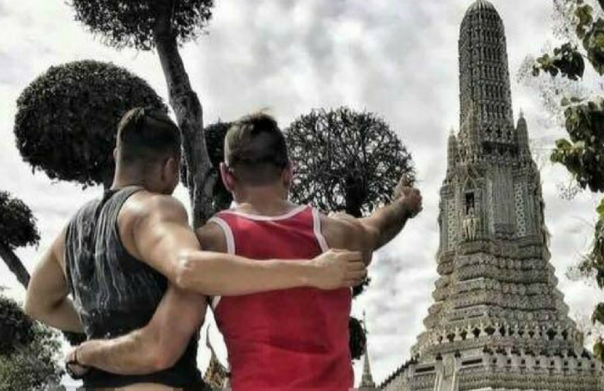 The couple posing in front of the Thai temple.