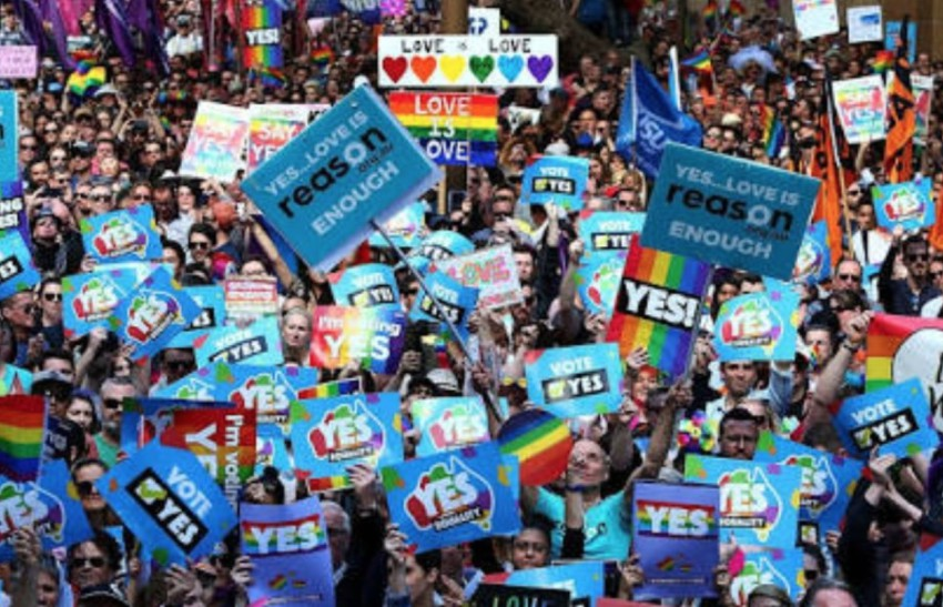 Australian marriage equality supporters holding 'yes' signs at a rally