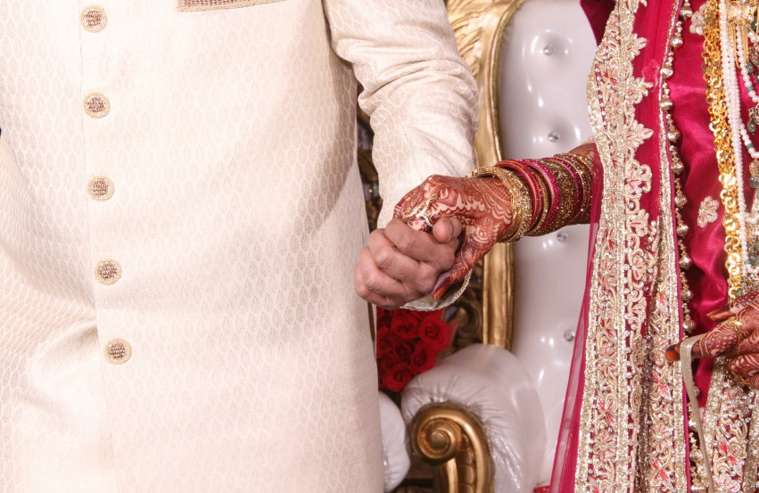 The torso and hand of an indian man and woman at a wedding ceremony