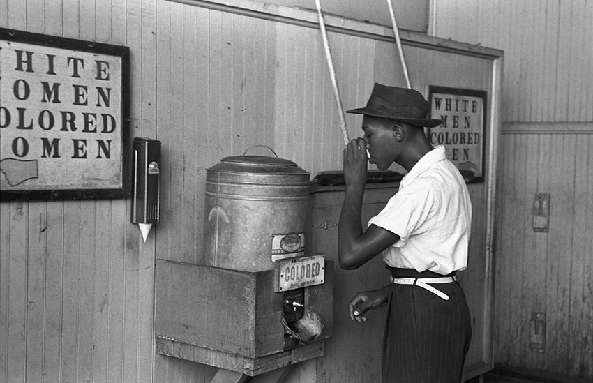 An African-American drinking at a 'colored' water fountain in 1939