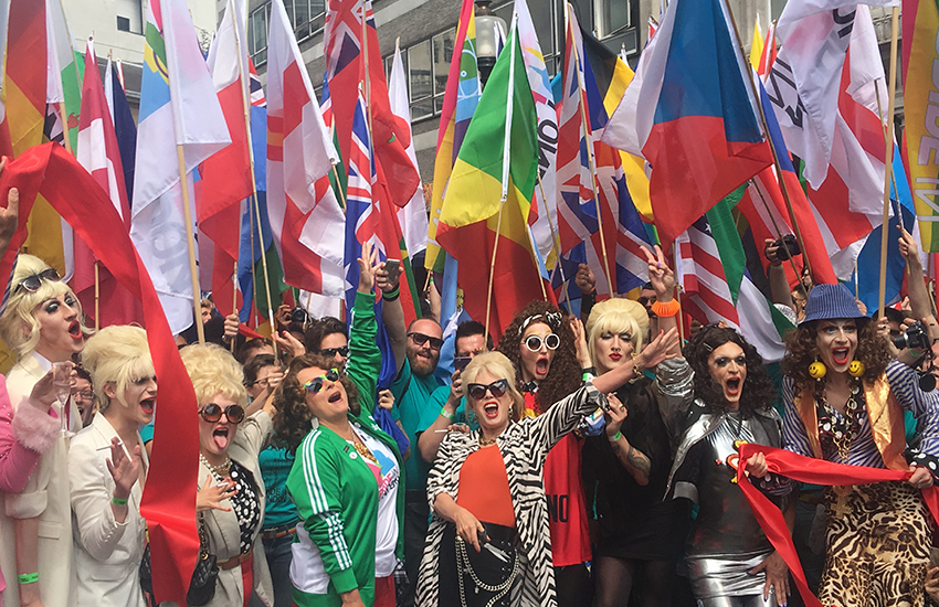 Marchers at Pride carrying flags from many nations.