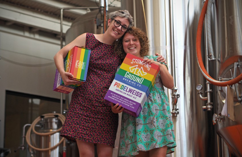Kelly Mackenzie and Kirsty Albion holding cases of beer at Stomping Ground brewery