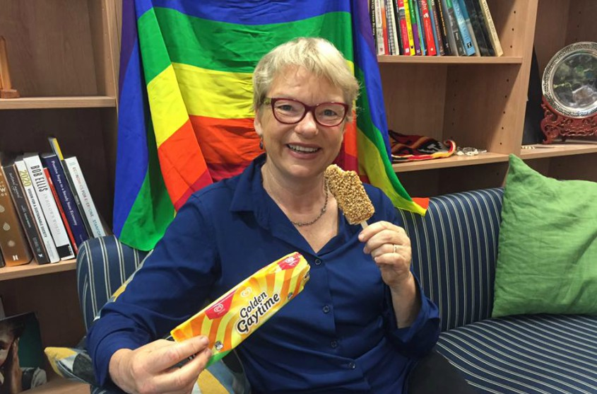 Australian senator Janet Rice eating a golden gaytime in front of a rainbow flag