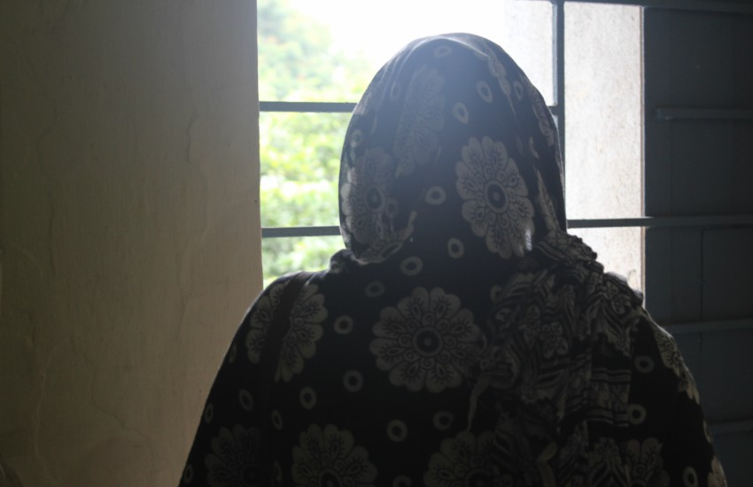 Rekha a trans woman in India looks out a window