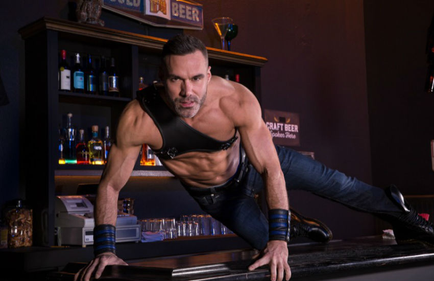 Gay porn actor Manuel Skye on top of a bar in a sexy pose