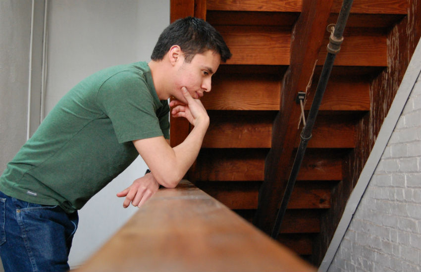 Man leans over bannister in thought