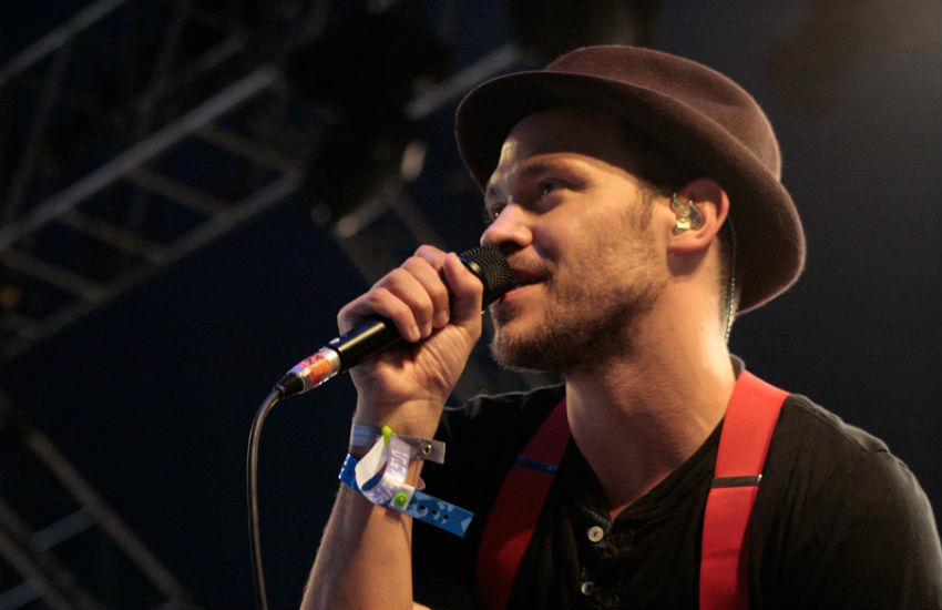 Will Young singing into a microphone at the Isle of Wight Festival 2009