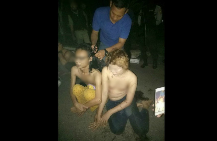 Blurred faces of two trans women sitting on the ground topless as a man cuts their hair