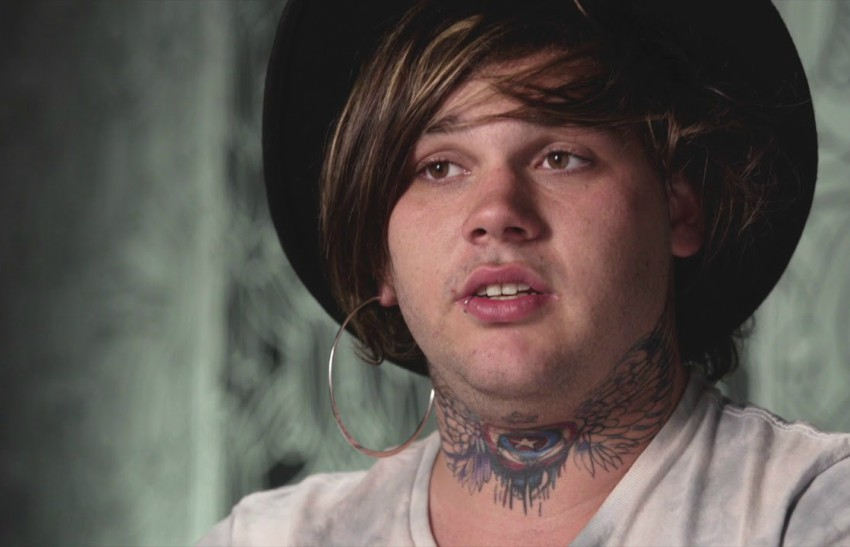 Young man with tattoos wearing black hat talking to the camera