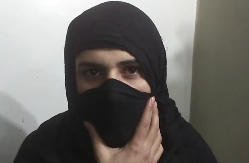 Trans woman wearing black hijab and holding material over her mouth with her hand