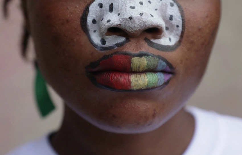Close up of girl with painted face and rainbow painted lips