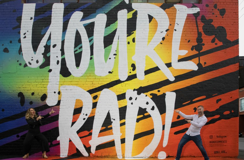 Two people posing on either side of a mural on a wall that read 'you're rad'. the writing is white with a rainbow background