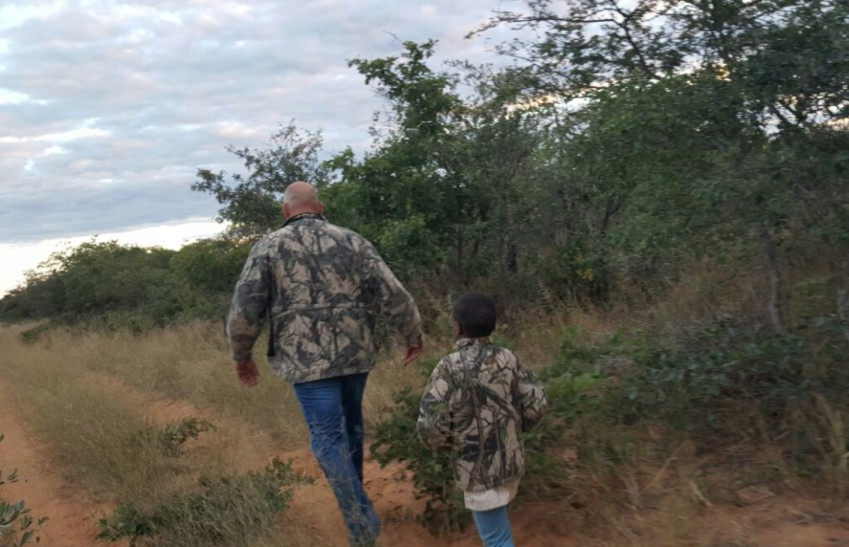 Man walking in front of child in bush landscape