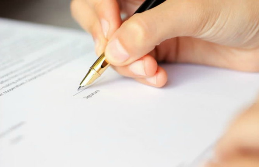 Hand signing a letter