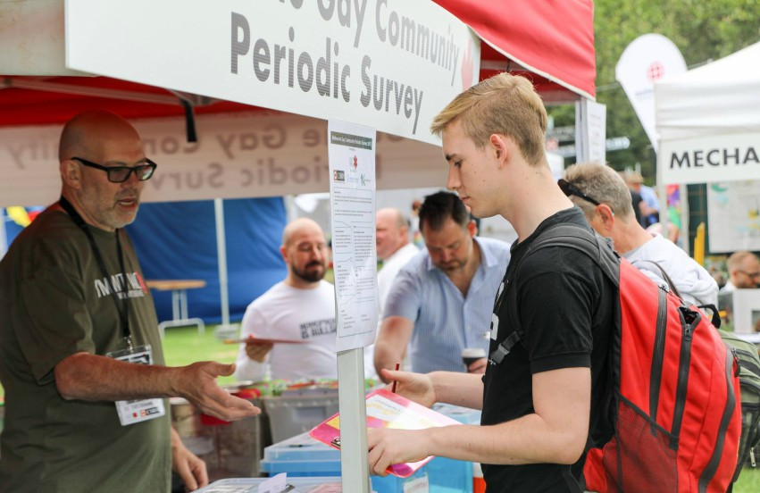 Man making enquiry at stall with older man responding to his questions