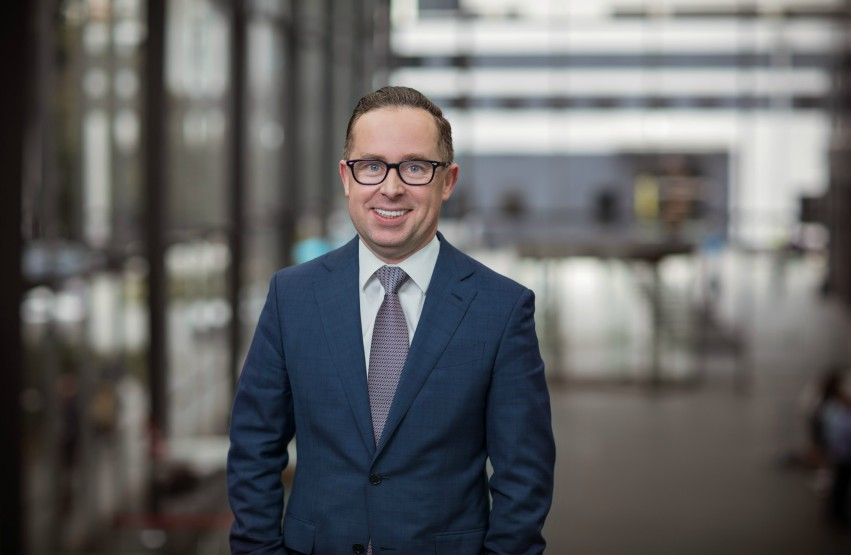 Qantas CEO Alan Joyce standing and smiling at the camera in a blue suit