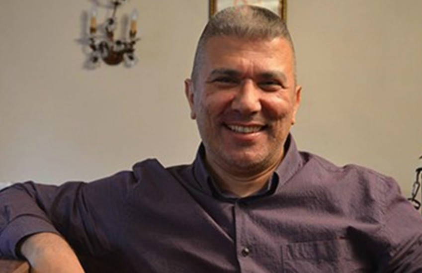 Ali Erol sitting in purple shirt smiling at the camera