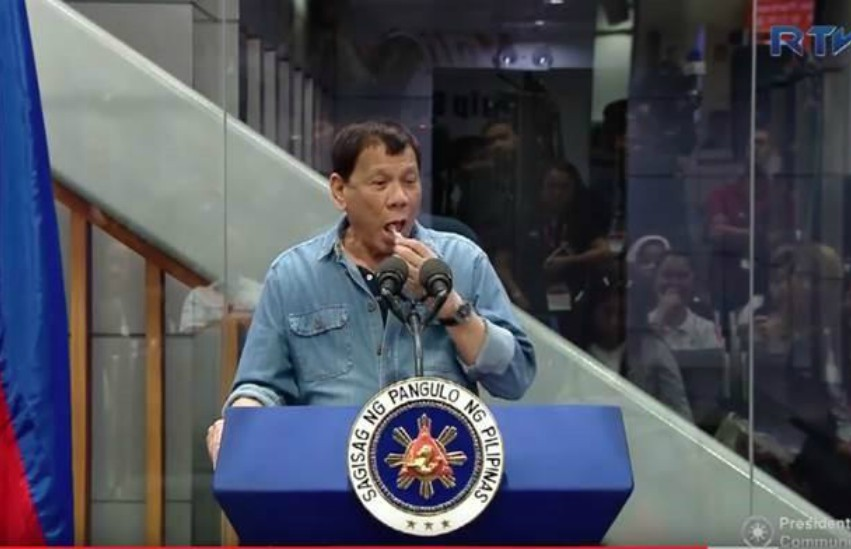 President Duterte standing behind blue lectern in denim shirt putting a still wrapped candy in his mouth