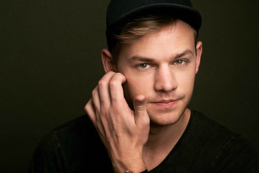 Close up of Joel Creasey's face wearing a black cap and black tshirt, he's scratching the side of his face with his right hand
