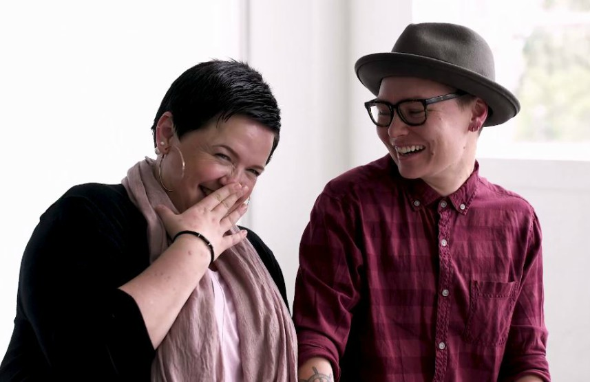Two people sitting next to each other and laughing together
