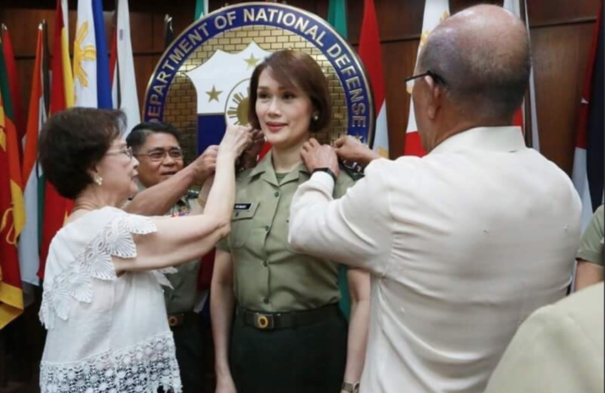 Geraldine Roman in military uniform with officials pinning things onto her shoulders