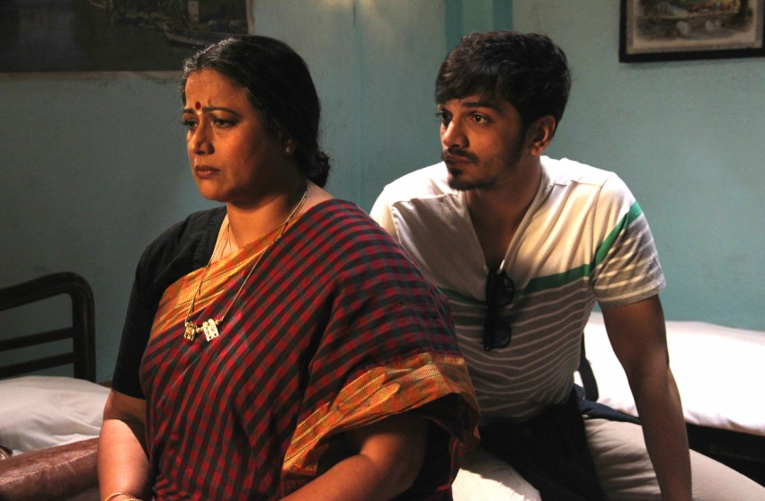 A woman frowning and sitting on a bed wearing a sari while a young man kneels behind her looking at her