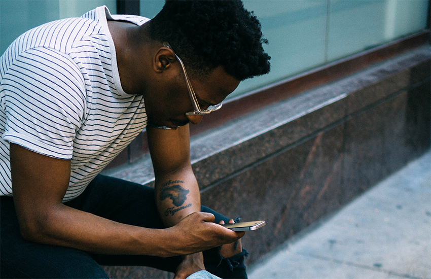 A man checks his cellphone - opinion column on HIV stigma