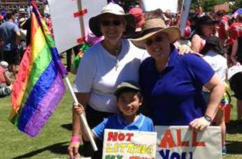 Young boy holding a rainbow flag and placard standing in front of two women also holding placards in support of marriage equality