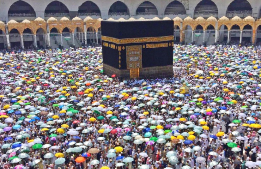 Holy site of Mecca surrounded by thousands of people holding colorful umbrellas