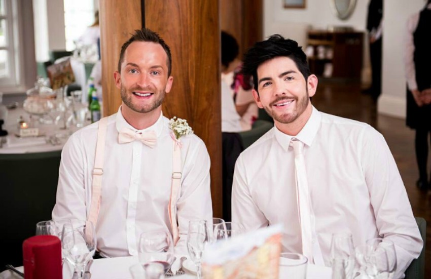 Two men sitting next to each other in white shirts