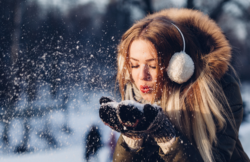 A woman in a large coat plays in the snow