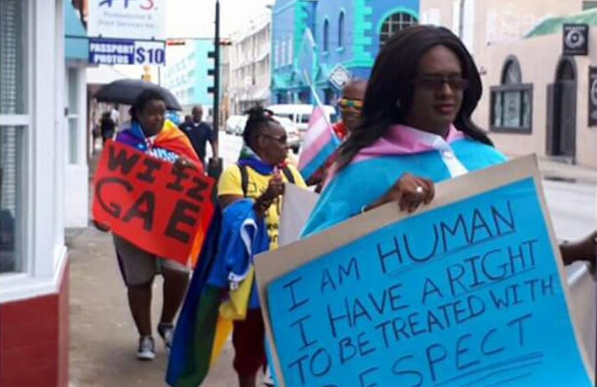 An activist holds a banner demanding human rights at Barbados Pride