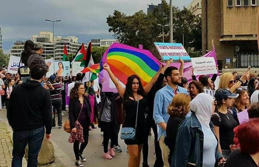 a street protest with people holding placards in the colour of the trans flags and also holding rainbow flags