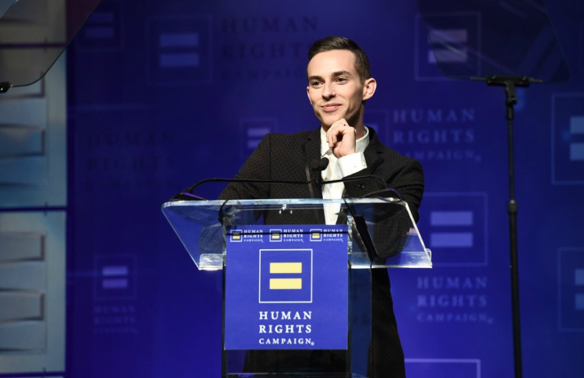 Adam Rippon behind HRC branded clear podium with his hand on his chin leaning on the podium