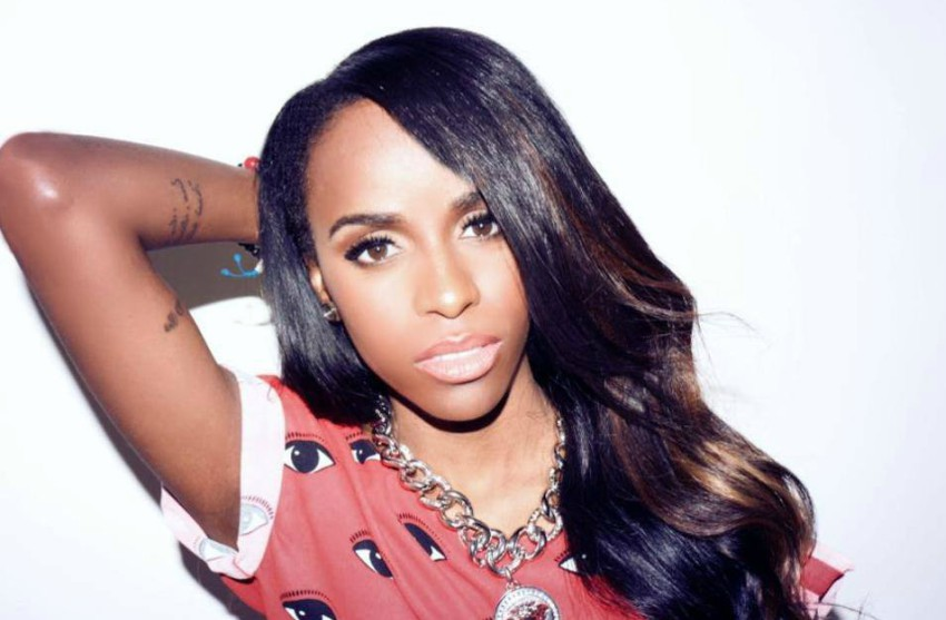 Angel Haze promo shoot. She's standing against a white backdrop with her right hand behind her head