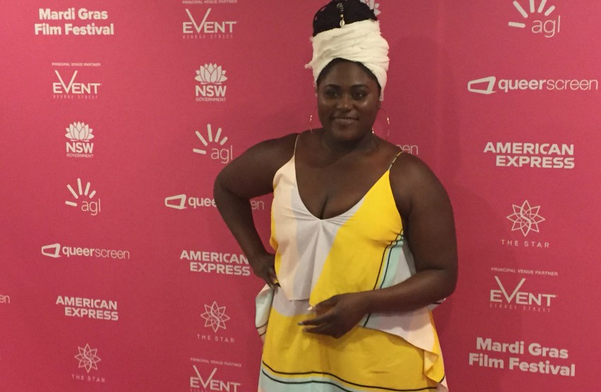 Danielle Brooks posing front of media wall