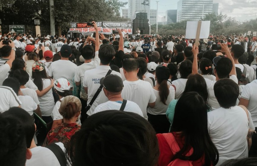 People in white t-shirts with backs to camera at street protest