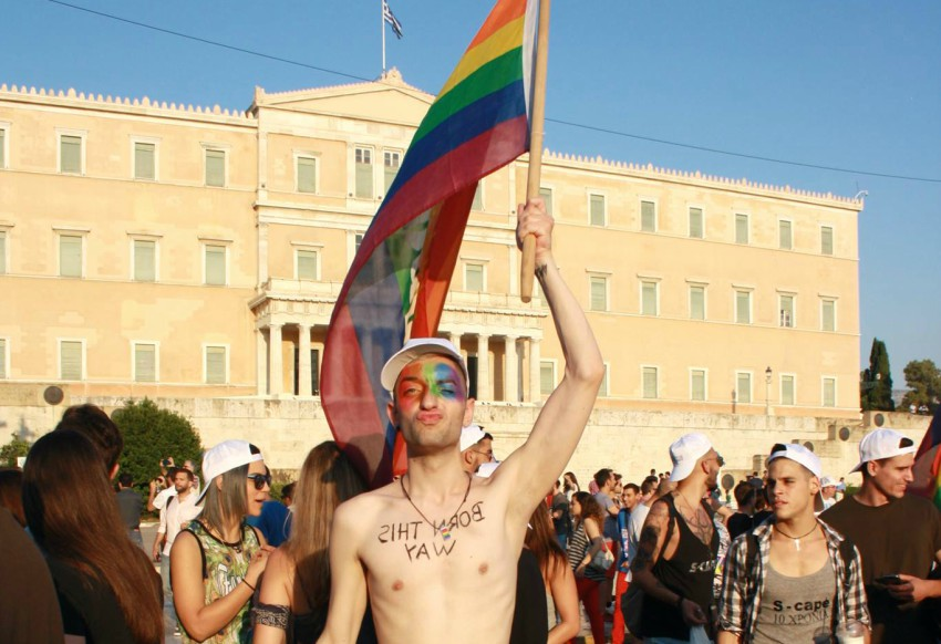A young man stands topless in front of Greece's parliament holding a rainbow flag over his head