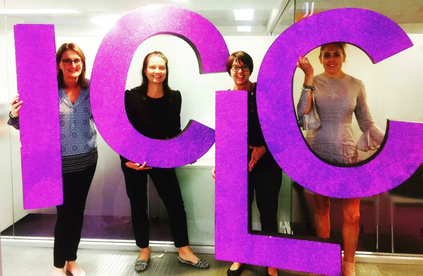 Fourt women stand against glass wall holding big purple letters that spell ICLC
